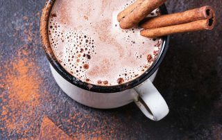a mug of hot chocolate with cinnamon sticks