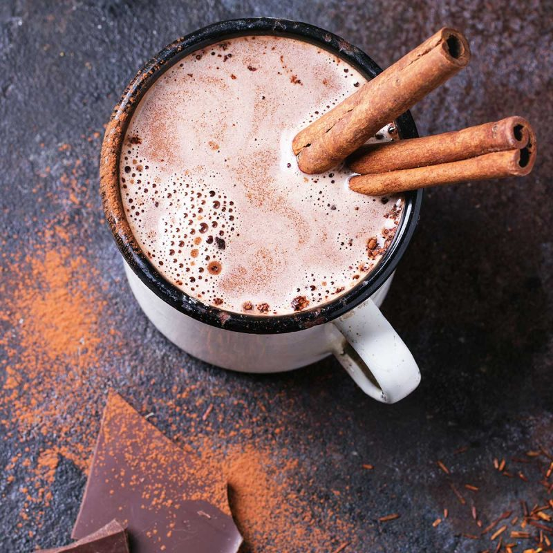 a mug of hot chocolate with cinnamon sticks
